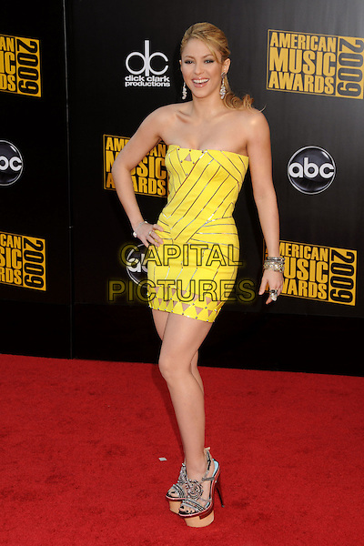 SHAKIRA (Shakira Isabel Mebarak Ripoll).The 2009 American Music Awards held at The Nokia Theatre L.A. Live in Los Angeles, California, USA. .November 22nd, 2009.AMA AMA's full length yellow mini strapless dress hand on hip platform sandals shoes .CAP/ADM/BP.©Byron Purvis/AdMedia/Capital Pictures.