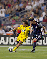 Columbus Crew forward Guillermo Barros Schelotto (7) passes the ball as New England Revolution midfielder Pat Phelan (28) defends. The New England Revolution tied Columbus Crew, 2-2, at Gillette Stadium on September 25, 2010.