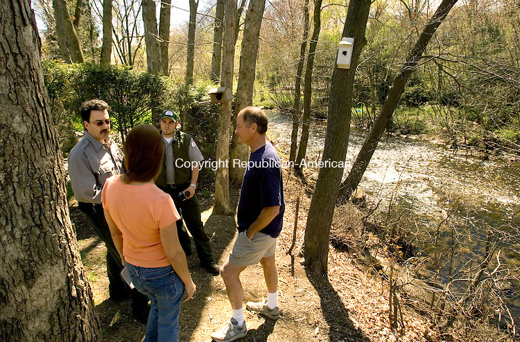 WATERBURY, CT--04 MAY 2007--050407JS04- Christopher Way, a project manager with the U.S. Army Corps of Engineer, and an unidentified U.S. Army Corps of Engineer worker, talks with Regal Court residents Suzanne Maia and Ron Marciano about the erosion that is occuring along the banks of the Mad River in Waterbury. <br /> Jim Shannon/Republican-American