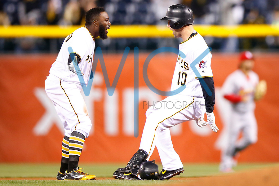 Jordy Mercer #10 of the Pittsburgh Pirates celebrates his walk-off hit with teammate Josh Harrison #5 of the Pittsburgh Pirates in the 11th inning against the St. Louis Cardinals during the game at PNC Park in Pittsburgh, Pennsylvania on April 5, 2016. (Photo by Jared Wickerham / DKPS)