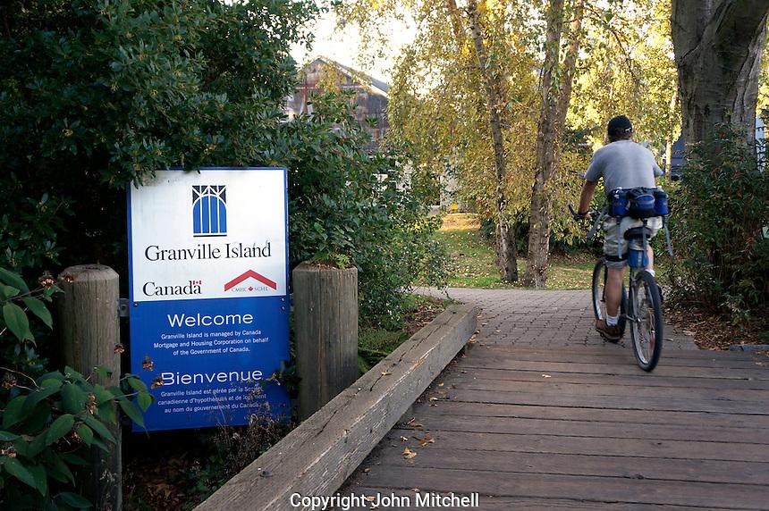 Male cyclist crossing a wooden bridge to Granville Island,, Vancouver, BC, Canada