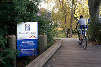 Male cyclist crossing a wooden bridge to Granville Island,, Vancouver, BC, Canada