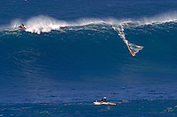 A tow-in surfer drops into Hawaii's big surf at Peahi (Jaws) off Maui, while his partner rides the crest on the jetski that did the towing.