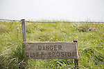 A wooden sign warning of the danger of cliff erosion at the top of the sheer cliffs at Beachy Head, East Sussex, England