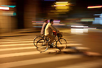 Two men ride their bikes down a street in central Shanghai at night.<br />