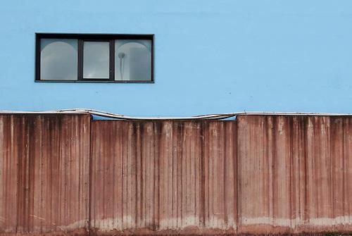 Taranto, Italie, Jan 2010.  Un mur du quartier de Tamburi, recouvert de poussiere rouge,  particules de metaux portees par le vent, provenant de la siderurgie ILVA. Tarente est la ville la plus polluée par émissions industrielles en Europe. A Tarente, chacun des 210 000 habitants respire chaque année 2,7 tonnes de monoxyde de carbone et 57,7 tonnes de dioxydes de carbones. Le quartier ouvrier de Tamburi, tout proche de la zone industrielle souffre très directement de la pollution industrielle. Image issue de la Serie La Poussiere Rouge.