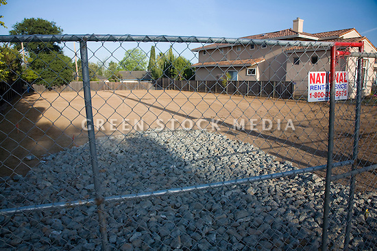 A small single-story home was cleared from this site in preparation for building a large two-story luxury home, viewed through a fence. Cupertino, California, USA