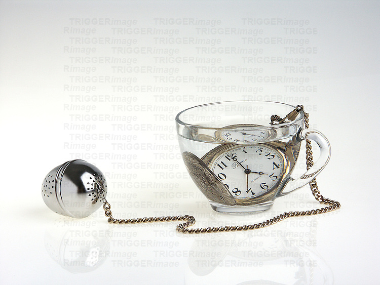 A glass tea cup with a pocket watch under water