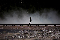 A tourist walks the boardwalk over the Grand Prismatic Spring in Yellowstone National Park, Wyoming on Tuesday, May 23, 2017. (Photo by James Brosher)