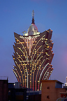 The distinctive golden facade of the Grand Lisboa casino, lit up at dusk.<br />
