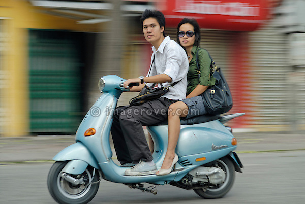 Asia, Vietnam, Hanoi. Hanoi old quarter. Cool young couple on Vespa motorbike rushing through Hanoi.