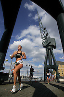 07 AUG 2005 - LONDON, UK - Jacqui Slack runs under the old dock cranes during the London Triathlon '05. (PHOTO (C) NIGEL FARROW)