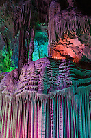 Limestone Flowstone formation in one of many of caves.  The colorful lighting serves to provide a Fantasyland experience, and is also thought to be less stressful to the formations compared to straight white light.  Near Guilin, Li River, May 2007.