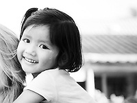 Black and white photo of a cute Thai girl, Koh Lanta, South Thailand. Waiting for our pick up to travel down to Penang, Malaysia, the owner of LD Beach Bungalow's children decided that piggy backs at 7.30am was exactly what the guests would enjoy! This girl was attached to Robyn like a limpet.