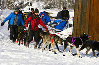Volunteers help lead John Bakers team out of village @ Takotna Chkpt 2006 Iditarod Alaska Winter