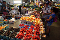 Couple buying fresh cherries at the Granville Island Public Market, Vancouver, BC, Canada