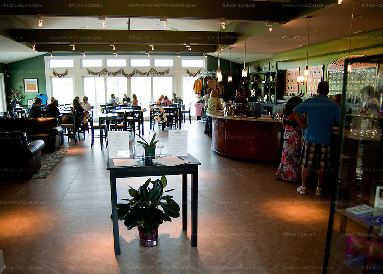 The tasting room at Narmada Winery resembles a restaurant or bistro, with tasting bar to one side, comfortable casual seating areas, tables at the back, and a wrap-around balcony/porch outside.