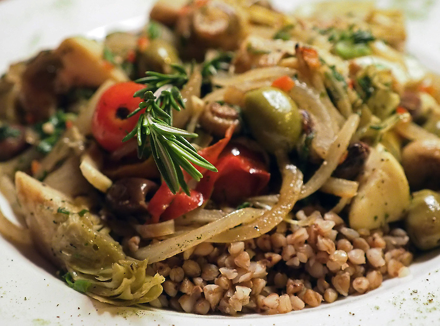 Vegetarian Givetch, composed of potatoes, mushrooms, onion, red pepper, olives, artichokes and garlic sautéed in a blend of southern Russian spices (note rosemary sprig) over buckwheat pilaf. Photo by Brad Stauffer
