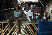 Ernesto Betasolo poses for a photo with his wife Antonita Betasolo (right) and his children and grand children in their house in Relocation Golden Valley in Barangay Pagkakaisa outside of Puerto Princesa, Palawan in the Philippines. <br /> Photo: Sanjit Das/Panos for Greenpeace