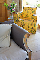 In the drawing room a moulded armchair is decorated in a yellow floral motif juxtaposed with a sofa covered in contemporary grey Indian linen