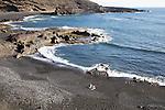 Two people sitting on black sand beach, El Golfo, Lanzarote, Canary Islands, Spain