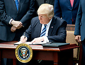 """United States President Donald J. Trump signs an Executive Order """"Promoting Free Speech and Religious Liberty"""" in the Rose Garden of the White House in Washington, DC on Thursday, May 4, 2017.<br /> Credit: Ron Sachs / CNP"""