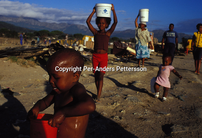 STRAND, SOUTH AFRICA - JANUARY 19: Unidentified children carries water in buckets from a water tap, a day after a shack fire on January 19, 2004, in a poor township outside Strand, South Africa. Shack fires are very common, as they are built very close to each other and people are using paraffin stoves, which easily fall over, and the fires spread quickly. About 300 shacks were burned to the ground in a couple of hours and about 1500 people were homeless and lost all their possessions. South Africa is facing a severe backlog of housing for the poor. The government has built about 1,7 million houses since 1994, but the backlog is still 6-7 million, still forcing people to live in dangerous shacks in appalling conditions without running water or electricity..(Photo: Per-Anders Pettersson/Getty Images)..