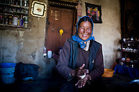 Rinchen's mother, Tsemang Dolma makes dough bread for breakfast in the 200 year old kitchen of Rinchen's house on 2nd June 2009. They run a home stay program in Ulley Valley, a scattered village of only 5 houses, one school, 38 people, 4 school children, and 4 pet dogs. The village is not accessible by road. The homestay program is managed by 'Snow Leopard Conservation Organisation', an NGO that helps families in the mountains that face constant snow leopard attacks on their live stock. Leh town is 3505m above sea level, in the Indian Himalayan mountains, in the valley of Ladakh, located in the Indian Himalayas, in the northern state of Jammu and Kashmir. Photo by Suzanne Lee