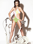 Fashion portrait of a beautiful slim woman wearing one-piece swimsuit standing behind a retro exercise bicycle isolated on white background Image © MaximImages, License at https://www.maximimages.com
