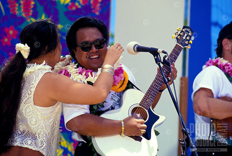 Woman giving musician a lei at the Hawaiian slack key guitar festival