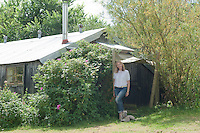 Carina Cooper standing outside the converted chicken shed with one of her whippet lurchers