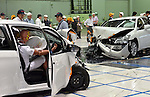 """July 21st, 2011, Susonosi, Japan - Toyota technicians check a badly damaged Crown, left, and a VITZ after a head-on collision at the speed of 55km/h (about 34 miles/h) in a demonstration at Toyotas Higashi-Fuji Technical Center on the foot of Mt. Fuji, some 92km (about 57 miles) southwest of Tokyo, on Thursday, July 21, 2011. Toyota showed to reporters technologies aimed at increasing safety for pedestrians and elderly drivers, as part of its initiatives to eliminate traffic casualties. The technologies include a Pre-Collision System with collision-avoidance assist, glare-preventing adaptive driving beams and a pop-up hood for lessening pedestrian injury. In the PCS, Toyota uses cameras and a super sensitive radar called """"millimeter-wave,"""" both installed in the front of the vehicle, to detect possible crashes such as a pedestrian crossing the road. Then the vehicle calculates how braking and steering must be applied to avoid a crash. (Photo by Natsuki Sakai/AFLO) [3615] -mis-."""