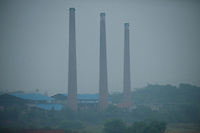 Daytime landscape view from a train of smoke stacks at a commercial heavy industry site near Wuhan in Hubei Province.  © LAN