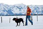 A young woman walks her dog along a country road in Jackson Hole, Wyoming.
