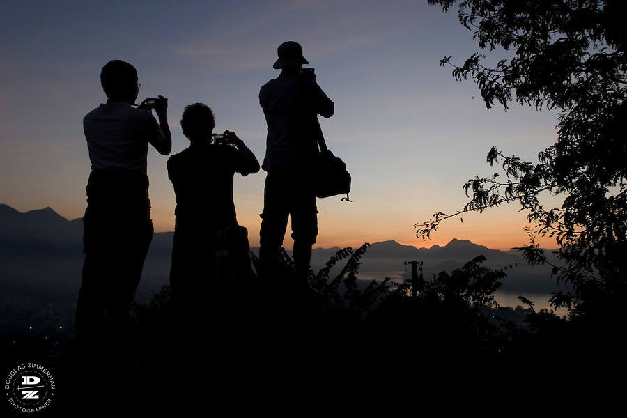 Tourists take photographs of the sunset at Phu Si Hill or Chomsy Hill, in central Luang Prabang, Laos. The hill is a popular place for tourists and locals to view the sunset over the hills surrounding the city.  Photograph by Douglas ZImmerman.