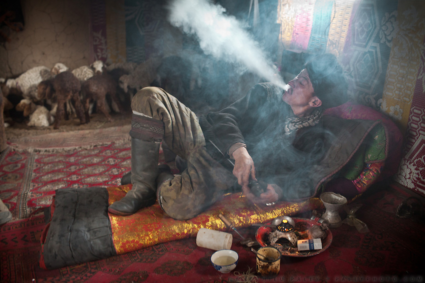 Aziz, one of the son of the late Khan, during one of his 3 daily opium smoking session, in his home. He is completely addicted, having smoked regularly since the last 8 years..Kyzyl Qorum, campment of the former deceased Khan, Abdul Rashid Khan..Trekking with yak caravan through the Little Pamir where the Afghan Kyrgyz community live all year, on the borders of China, Tajikistan and Pakistan.