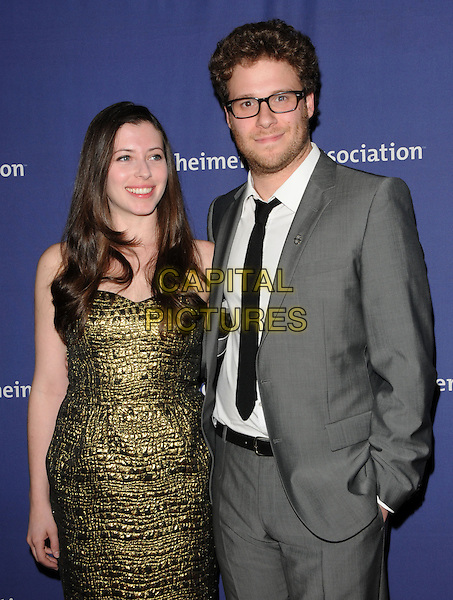 "LAUREN MILLER & SETH ROGEN .at The 18th Annual ""A Night at Sardi's"" Fundraiser & Awards Dinner held at The Beverly Hilton Hotel in The Beverly Hills, California, USA, March 18th 2010..half length gold green dress grey gray suit black tie glasses couple beard facial hair stubble                                                   .CAP/RKE/DVS.©DVS/RockinExposures/Capital Pictures."