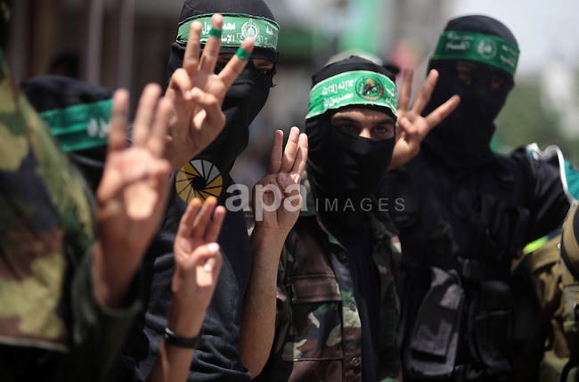 Palestinian Hamas militants flash three-fingered sign in reference to the three Israeli teenagers missing in the West Bank during a demonstration in solidarity with prisoners held in Israeli jails, and in support of the people in the West Bank, in Nuseirat refugee camp in the center of the Gaza Strip, June 20, 2014. Israel has launched a wide-ranging military operation aimed at finding the Israeli teenagers that believed kidnapped by Hamas and crushing the movement's infrastructure in the West Bank. Photo by Ashraf Amra