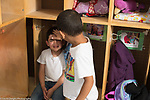 Education preschool 3-4 year olds empathy boy reaching out to pat forehead of crying boy sitting in cubby