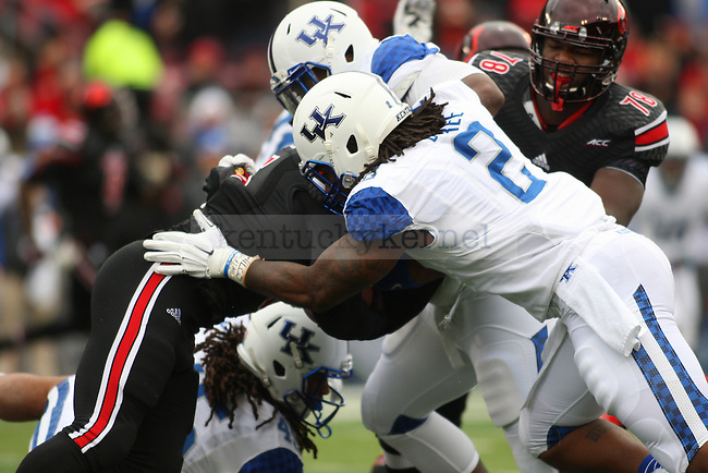 Defensive end Bud Dupree of the Kentucky Wildcats tackles a running back during the first half of the game against the Louisville Cardinals at Papa Johns Cardinals Stadium on Saturday, November 29, 2014 in Louisville, Ky. Photo by Michael Reaves | Staff