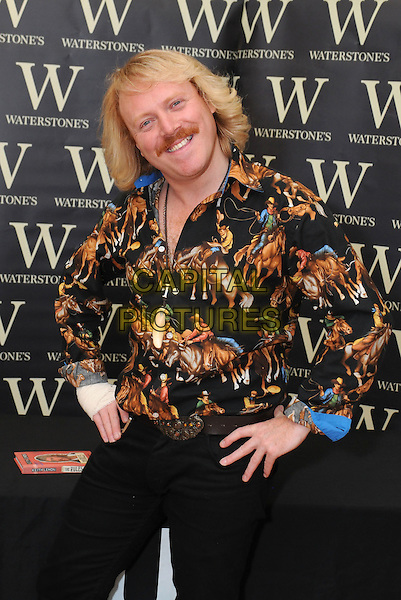 Keith Lemon (Leigh Francis).signs copies of his new book 'The Rules' at Bluewater Shopping Centre, Greenhithe, Kent, England, UK,.7th October 2011..half length cowboy print shirt facial hair moustache mustache  bandage black trousers  hands on hips .CAP/BRC.©Ben Rector/Capital Pictures.