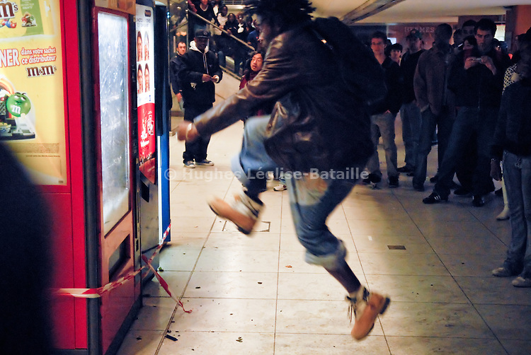 A youth is vandalizing a vending machine within the underground galleries of the Gare du Nord train station during the riot of March 27, 2007.