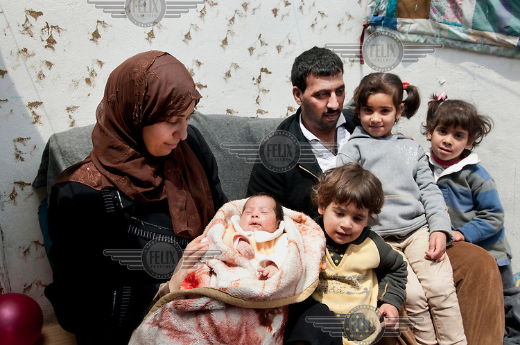 Samah, 24 (left) and her husband Darwish, 34, with their four children in the house they are renting in Amman. They fled the civil war in neighbouring Syria. /Felix Features