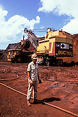 Carajas mine, Para State, Brazil. Man at excavation of iron ore from opencast mine with dumper truck and mechanical shovel.