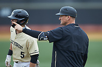Wake Forest Demon Deacons volunteer assistant Joey Hammond (29) looks to third base coach Tom Walter (not pictured) for the signs as Patrick Frick (5) takes his lead off of first base during the game against the Notre Dame Fighting Irish at David F. Couch Ballpark on March 10, 2019 in  Winston-Salem, North Carolina. The Demon Deacons defeated the Fighting Irish 7-4 in game one of a double-header.  (Brian Westerholt/Four Seam Images)
