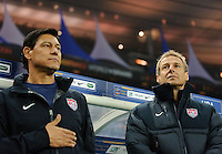 Jurgen Klinsmann, coach of team USA, and assistant coach Martin Vasquez stand for the national anthem prior to the friendly match France against USA at the Stade de France in Paris, France on November 11th, 2011.