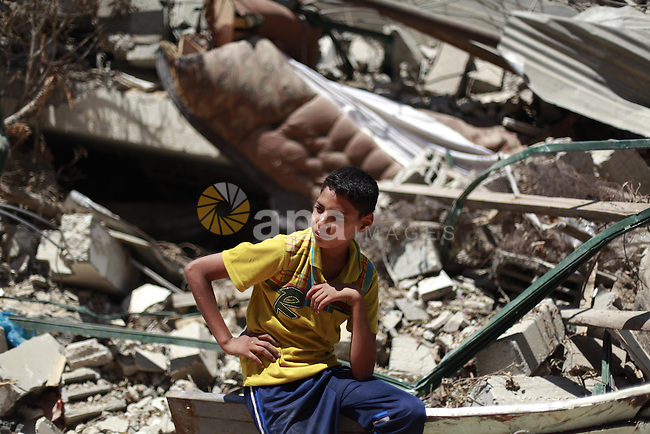 "A Palestinian boy sits on the debris of his family's house after it was hit by an Israeli military strike in Gaza city on August 10, 2014. A senior Hamas official said there was a ""weak"" possibility that Gaza truce talks would succeed and that Palestinian negotiators could leave Cairo after a meeting with Egyptian mediators. Photo by Ezz Zanoun"