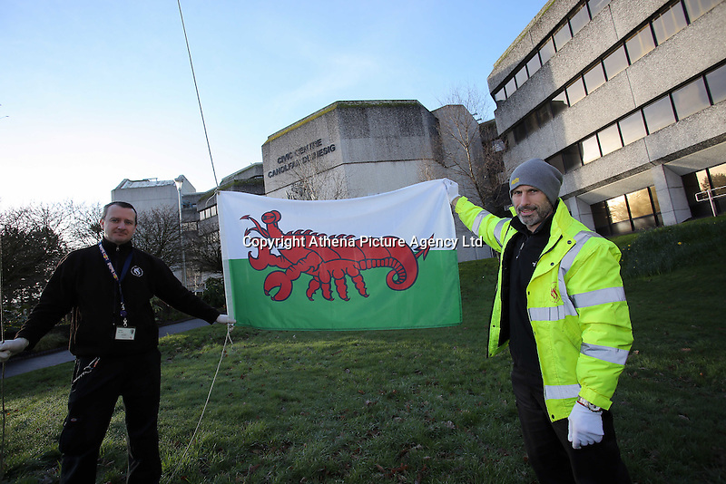 (L-R) Adrian Walters and H Jones raise a Wales flag in the shape of a red lobster instead of a red dragon is raised outside the Civic Centre, to raise awareness for Skin Care Cymru, in Swansea, Wales, UK. Tuesday 28 February 2017