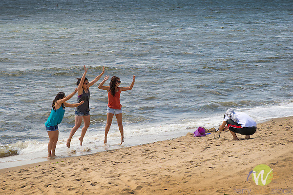 Hammonasset Beach State Park, New Haven County, Madison, Connecticut. Teens girls jumping and posing for picture