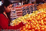 College student female shopping for fruit: citrus at outside display